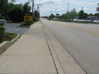 The sidewalk where the kids walked past the car dealerships.